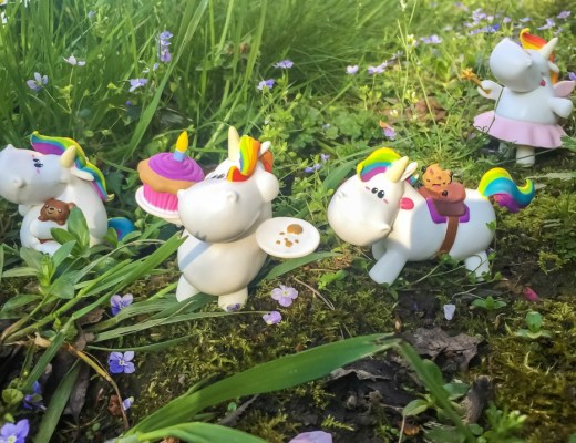 A photo of four bullyland Chubby Unicorn Figurines in the overgrown grass, forget-me-nots and daisies of a garden - Bullyland Chubby Unicorn Figurines - A Review - Mrs H's favourite things