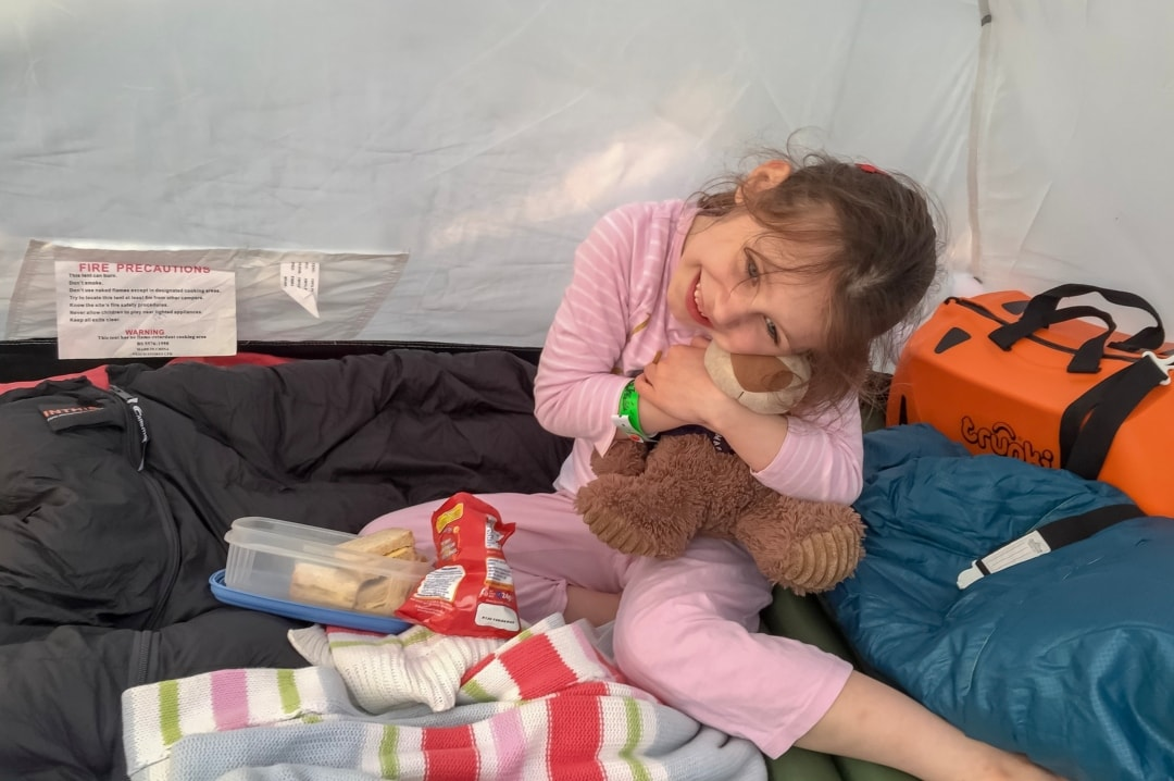A photograph of a little girl and her school bear eating a picnic tea in her tent at Elderflower Fields Festival - Our First Family Festival and Our Festival Essentials - Mrs h's favourite things
