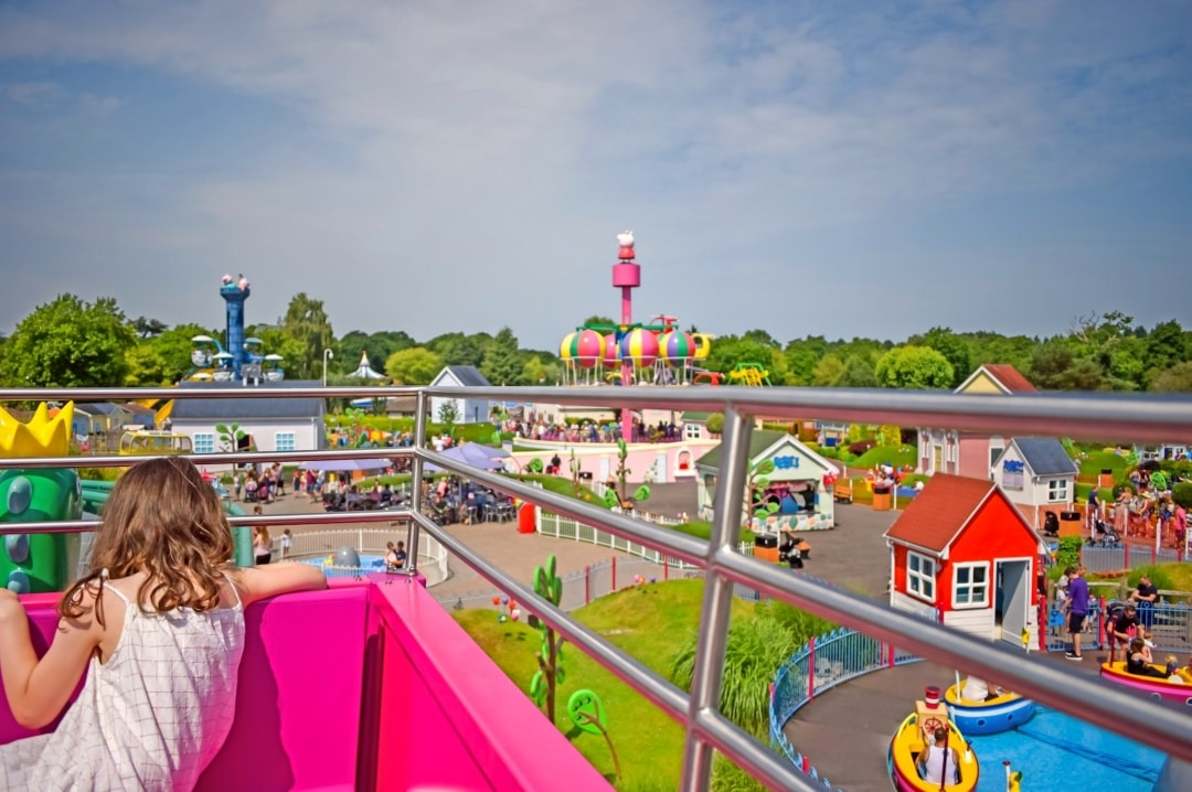 A photograph of a little girl on The Queen's Flying Coach Ride at Peppa Pig World in Paultons Park looking over Peppa Pig World - Paultons Park and Peppa Pig World - A Review - Mrs H's favourite things