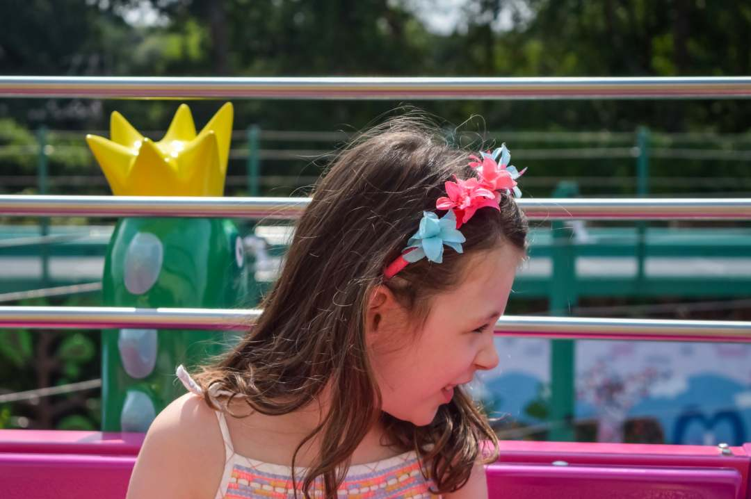 A photo of a little girl sitting in a themed carriage in The Queen's Flying Coach Ride in Peppa Pig World at Paultons Park - Paultons Park and Peppa Pig World - A Review - Mrs H's favourite things