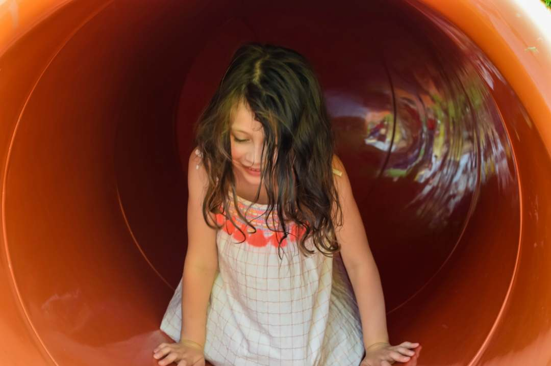 A photograph of a young girl going through a large tunnel in Mr Potato's Playground at Peppa Pig World in Paultons Park - Paultons Park and Peppa Pig World - A Review - Mrs H's favourite things