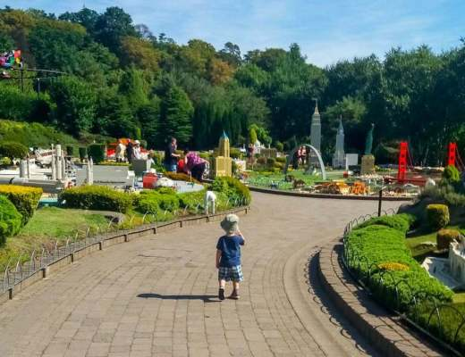 A brightly coloured photograph of a little boy toddling through Miniland at LEGOLAND Windsor Resort - LEGOLAND Windsor Resort - A Review - Mrs H's favourite things