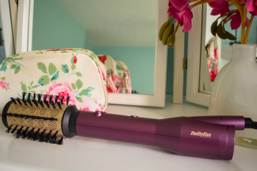 A photograph of the brand new BaByliss Bog Hair Care Airstyler sitting on a white dressing table by some mirrors and a vase of pink flowers - Love Your Hair With The Brand New BaByliss Big Hair Care - Mrs H's favourite things