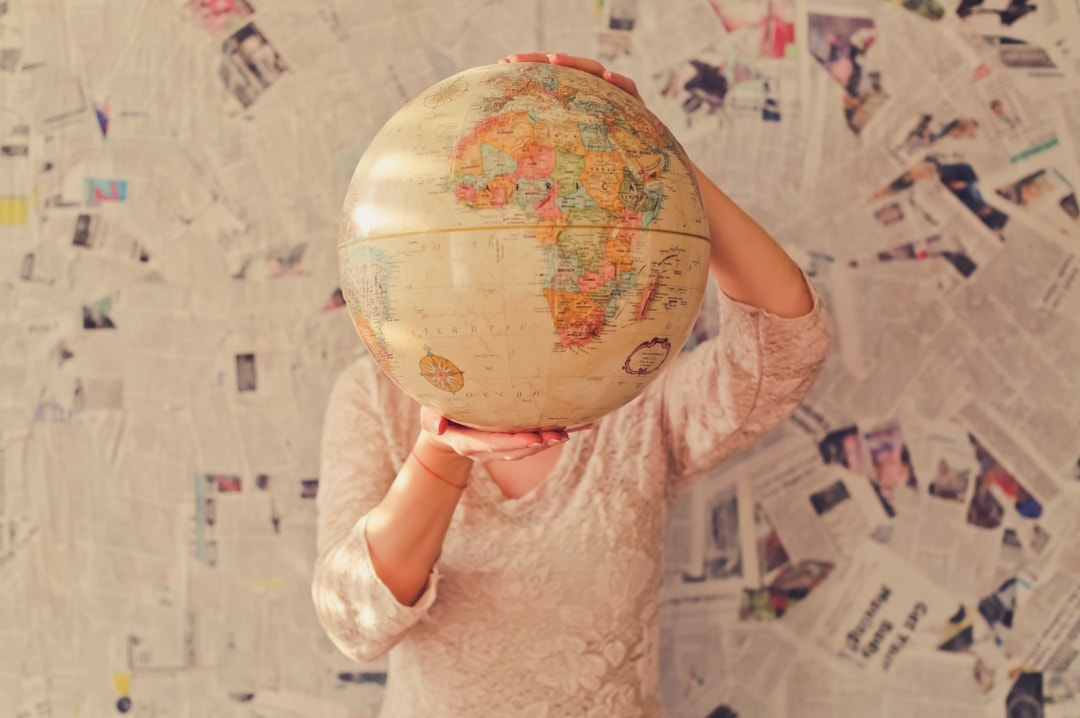 A photograph of a woman holding a globe in front of her face - Is It Time To Tackle Your Travel Bucket List? - Mrs H's favourite things