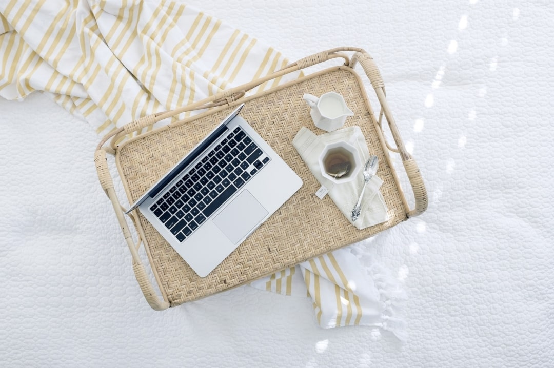 A photograph of a laptop and a coffee cup on a tray lying on a bed - Can The Internet Improve Your Health And Wellbeing? Mrs H's favourite things
