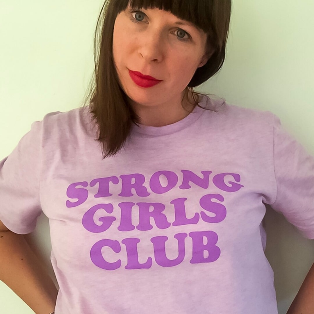 A photograph of a woman wearing a lilac Strong Girls Club t-shirt from Mutha.Hood - Finding Happiness and Chasing rainbows - September 2018 - Mrs H's favourite things