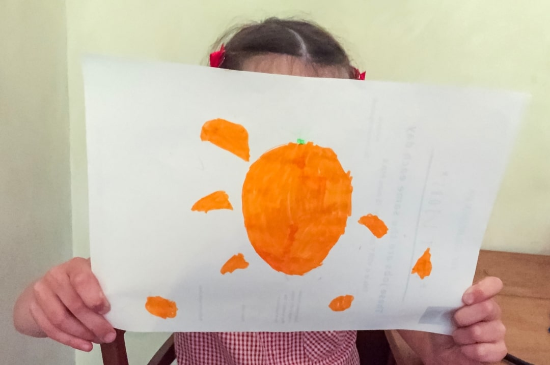 A photograph of a little girl showing off her drawing of what Bassetts Vitamins Omega-3 + Multivitamins Orange Flavour Pastille - Jumping At The Chance To Try With Bassetts Vitamins Omega-3 + Multivitamins Orange Flavour Pastilles taste like_ Jumping For The Chance To Take Bassetts Vitamins Omega-3 + Multivitamins Orange Flavour Pastille - Jumping At The Chance To Try With Bassetts Vitamins Omega-3 + Multivitamins Orange Flavour Pastilles - Mrs H's favourite things