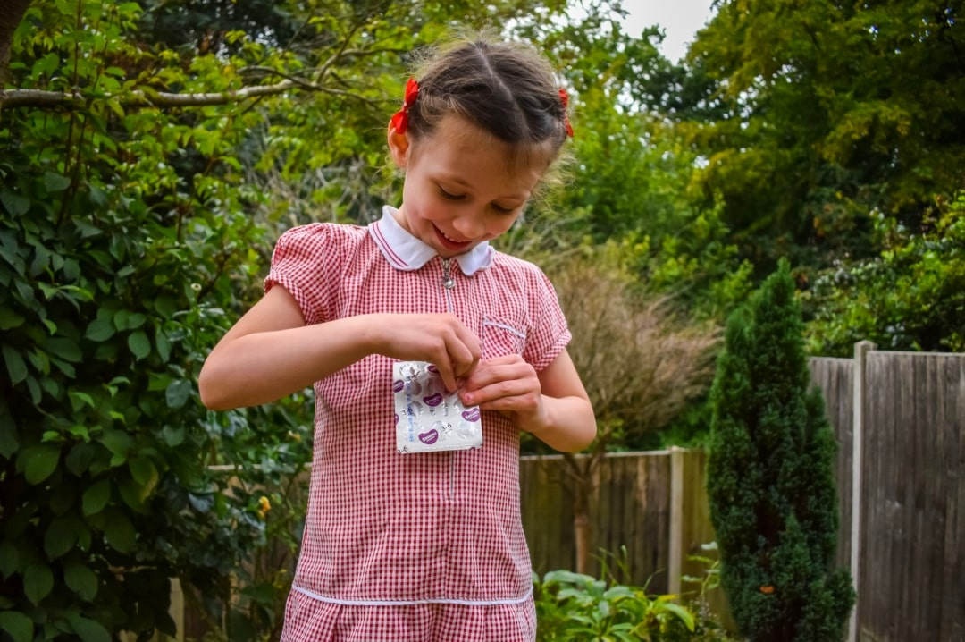 A photograph of a little girl trying to get a vitamin out of a packet of Bassetts Vitamins Omega-3 + Multivitamins Orange Flavour Pastilles - Jumping At The Chance To Try Bassetts Vitamins Omega-3 + Multivitamins Orange Flavour Pastilles - Mrs H's favourite things