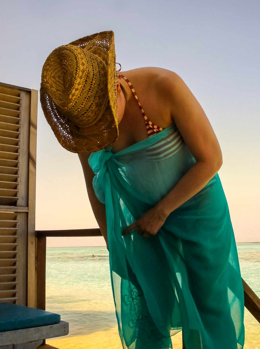 A photograph of a lady leaning out of a water villa as the sun sets in the Maldives - My Favourite Holiday - Our Honeymoon In The Maldives _ Mrs H's favourite things