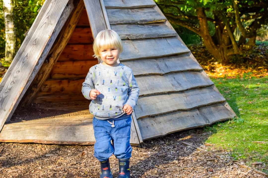 A photograph of a little boyplaying in a wooden teepee at the Slimbridge Wetlands Centre - Finding Happiness And Chasing Rainbows - Mrs h's Favourite things