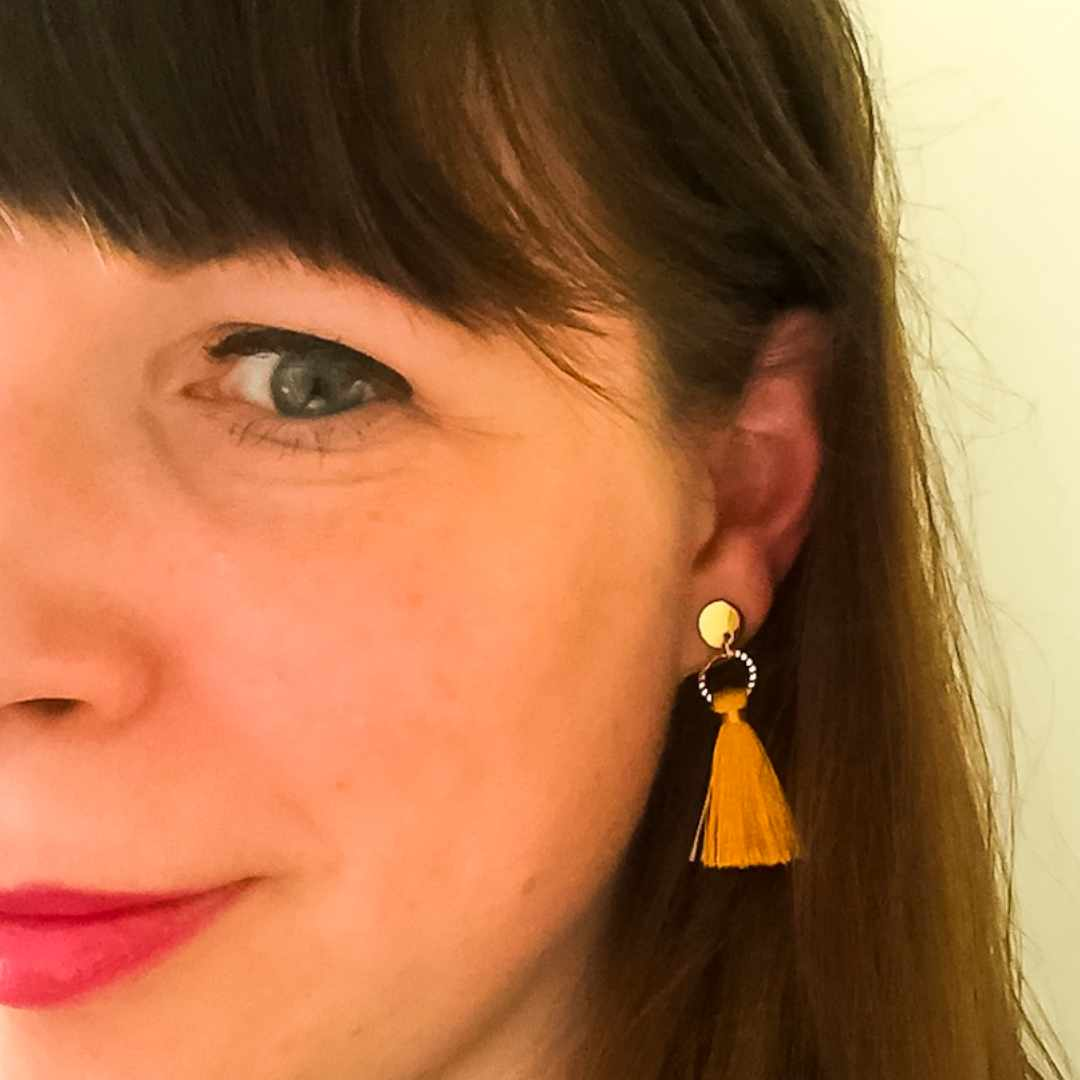 A photograph of a woman wearing mustard yellow dangly earrings - Finding Happiness And Chasing Rainbows - Mrs H's Favourite things