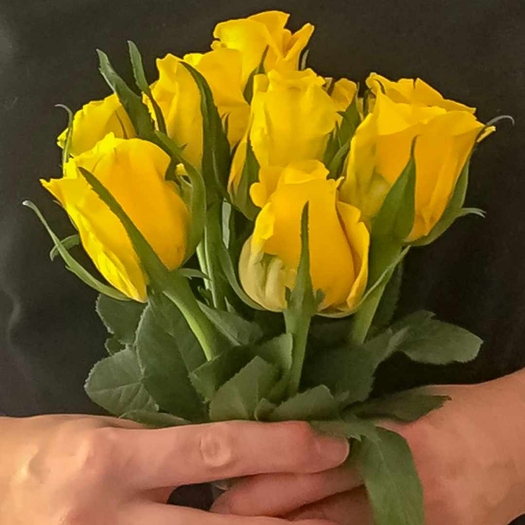 A photograph of a woman in a black top holding a bunch of yellow roses - Finding Happiness And Chasing Rainbows - Mrs H's Favourite things