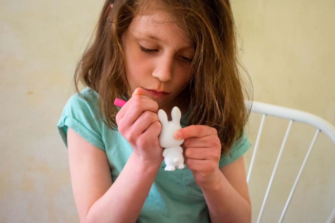 A photograph of a little girl drawing a design on a Fuzzikins Bedtime Bunny - Fuzzikins Bedtime Bunnies Review - Mrs H's favourite things