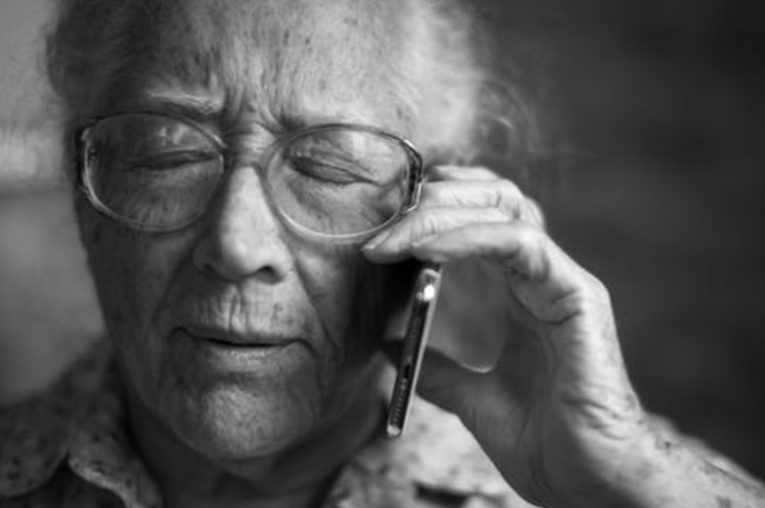 A black and white photograph of an elderly lady with a mobile phone - Choosing A Hearing Device - Mrs H's favourite things