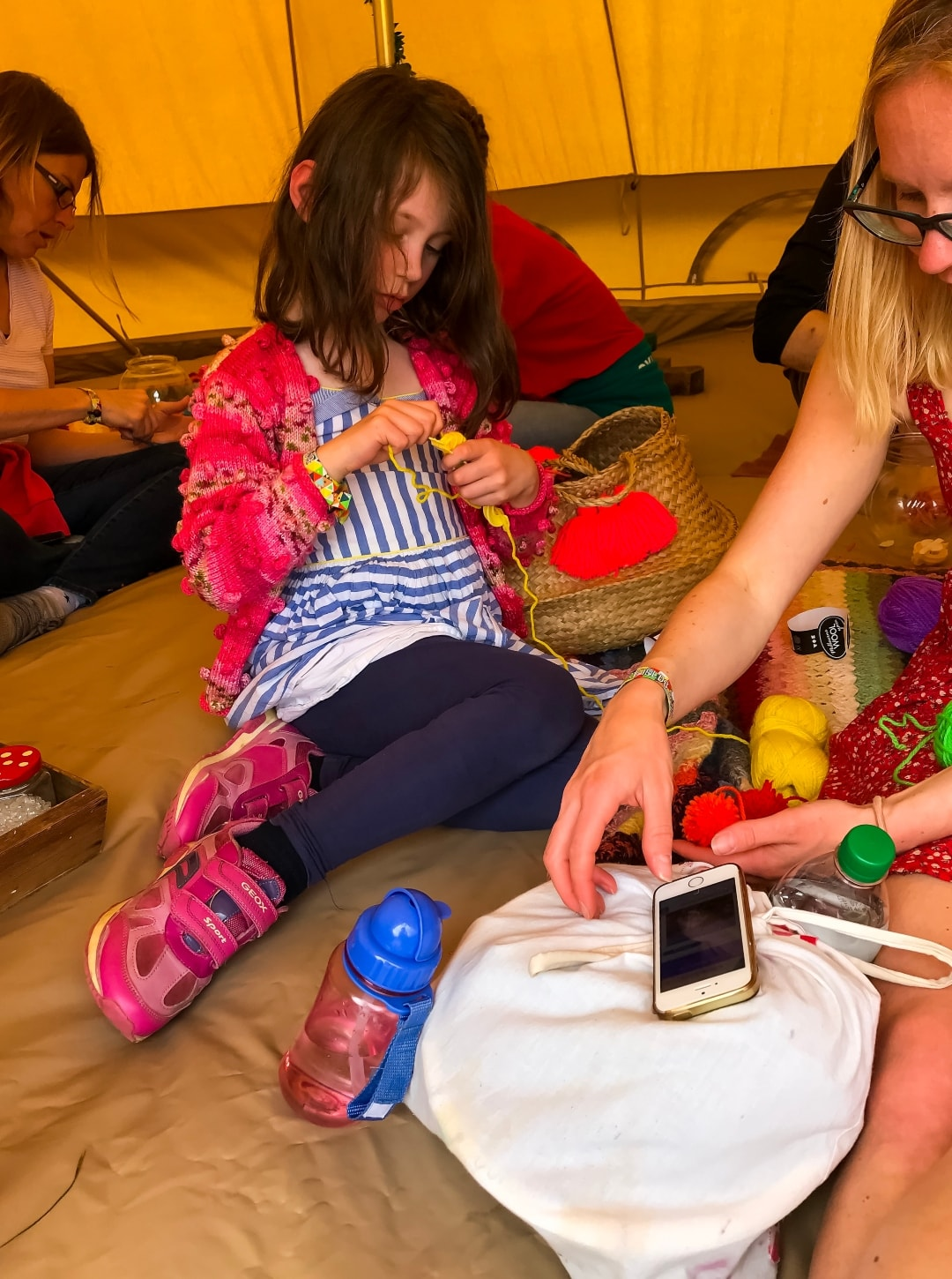 A photograph of a little girl making Pom Poms in a festival tent at the Elderflower Fields Festival - Elderflower Fields: The Perfect Family Festival - Part One - Mrs H's favourite things