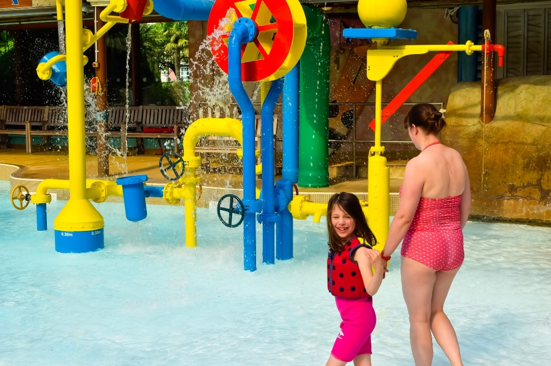 A photograph of a mother and her daughter at Splash Landings in Alton Towers - the little girl is wearing the Original Konfidence Swim Jacket and Konfidence Warma Wetsuit - Swimming With Konfidene At Splash Landings - Mrs H's favourite things