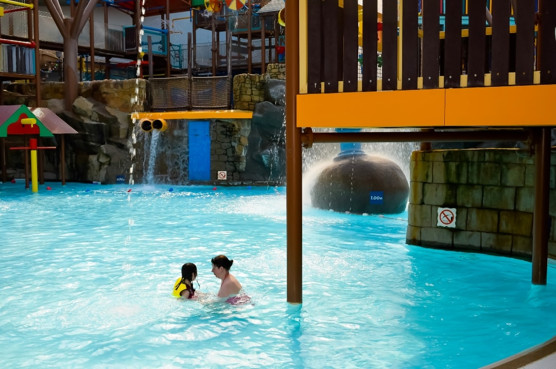 A mother and her daughter swimming at Splash Landings water park in Alton Towers . The little girl is wearing flotation devices and swimwear from Konfidence UK. Swimming With Konfidence At Splash Landings - Mrs H's favourite things