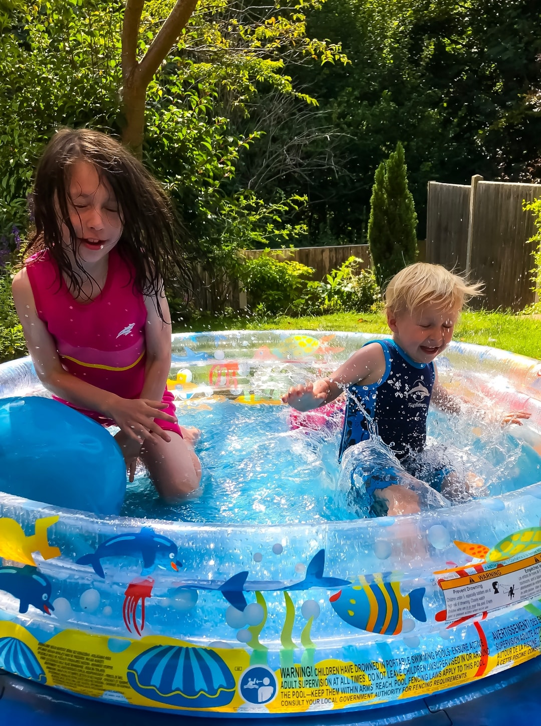 A photograph of a little girl and a little boy playing in a paddling pool - Snapshots Of Our Summer - Mrs H's favourite things