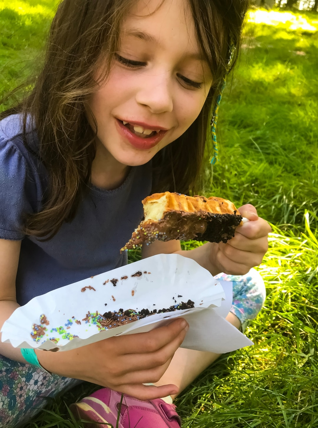 A photograph of a little girl eating a waffle on a stick at Into The Trees festival - Into The Trees 2019 - An Idyllic Family Festival - Mrs H's favourite things