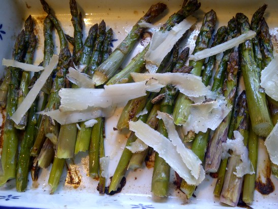 Image of roasted asparagus scattered with shards of goats' cheese