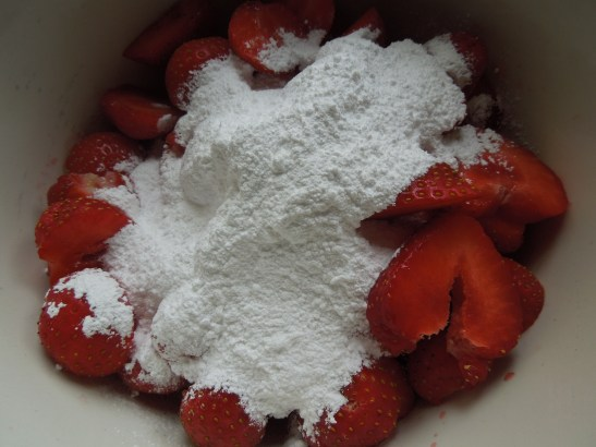 Image of sliced strawberries and icing sugar in a bowl