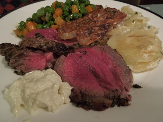 Image of beef fillet sliced and served with dauphinoise potatoes and braised peas and carrots
