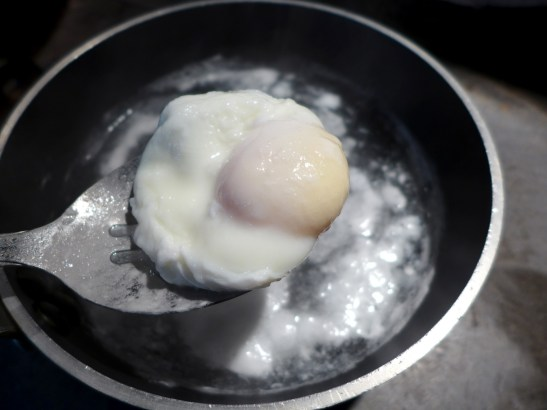 Image of poached egg scooped out with slotted spoon