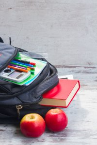 School backpack with supplies and two apples on white desktop