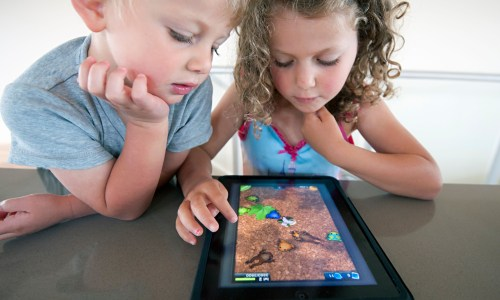 A young boy and girl staring at a tablet and playing a game