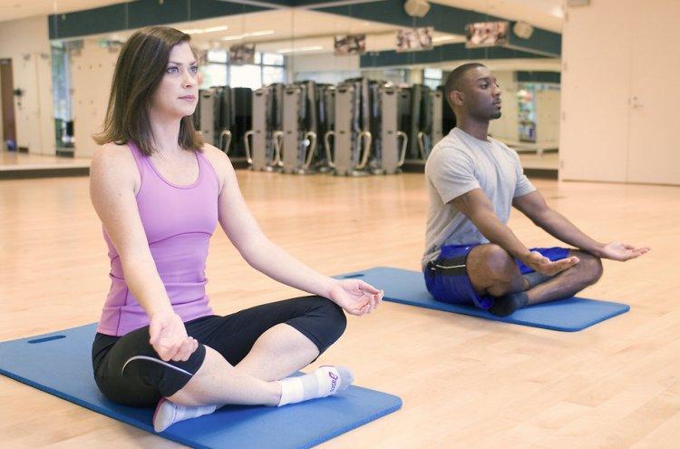 white woman and black man doing yoga at a gym studio