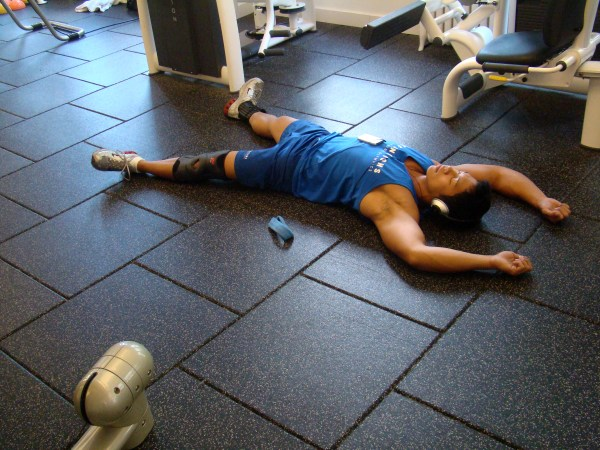 Guy exhausted from working out laying on the floor