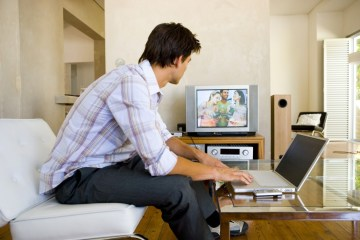 Man working from home looking at TV