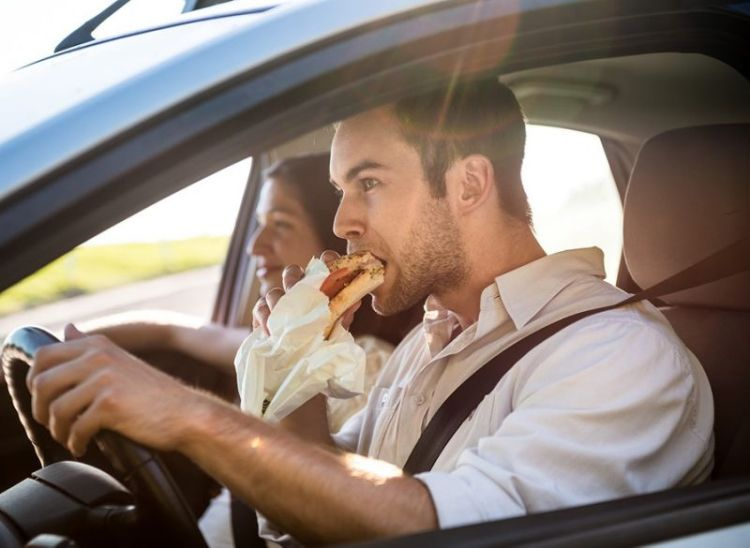 Guy eating a burger while driving his car