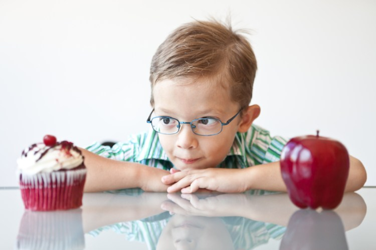 A little boy choosing between a cupcake and apple...looks like the cupcake is the winner.