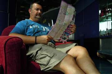 Man seating down in a lounge while reading