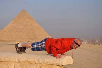 Guy doing a push up plank near a pyramid in egypt
