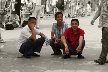 Group of men in china squatting down as they talk on a sidewalk
