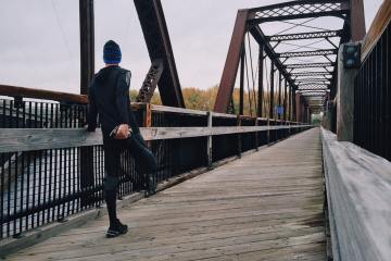 Biggest Mistake When Starting A New Workout Plan by Mr. Travel Fitness, shows a jogger stretching on a bridge