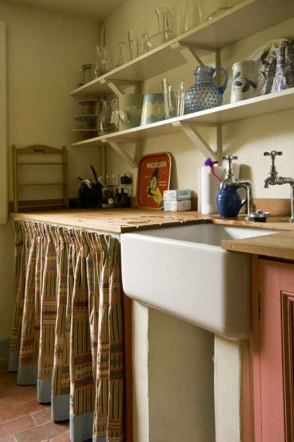 Vntage style kitchen with butler sink and curtained off section below draining board