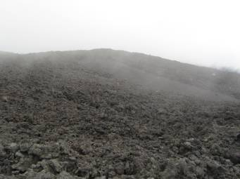 It is cold at the top of Etna and cloud floats over the most recent lava flow.