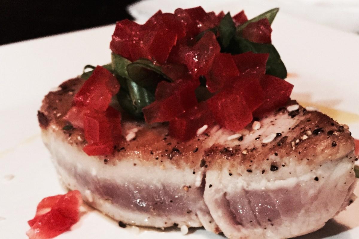 Filete de atún sellado a la parrilla con ajonjolí blanco, cebolla en rama, tomate concasse.