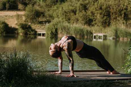 flexible tattooed woman standing in upward plank pose
