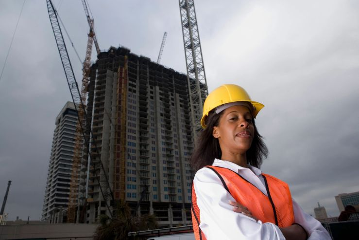 BE THE CHANGE! Woman in hard hat with satisfied look outside new construction hi rise building.