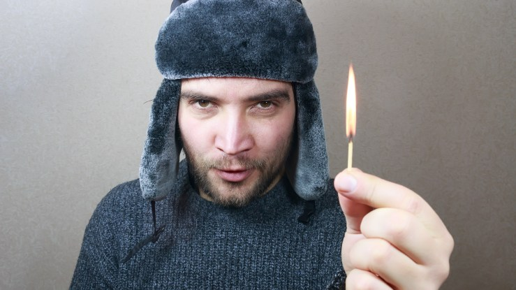 Jeez, light a match guy with winter hat on holding a lit match