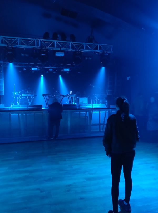 Photo of Millie standing in an empty venue room, waiting for FM-84 to perform their first ever European concert.