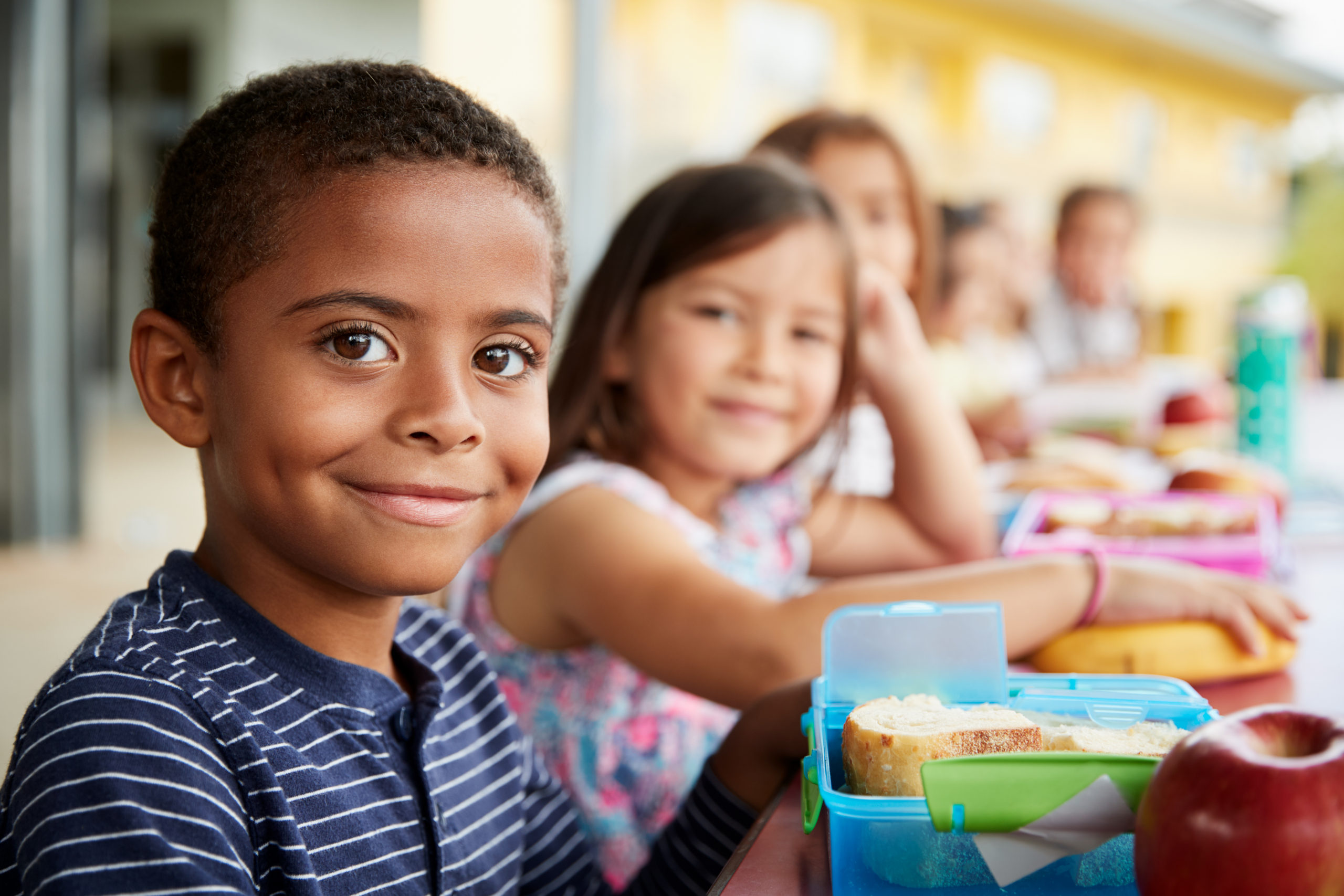 Children at school smiling at the lunch table
