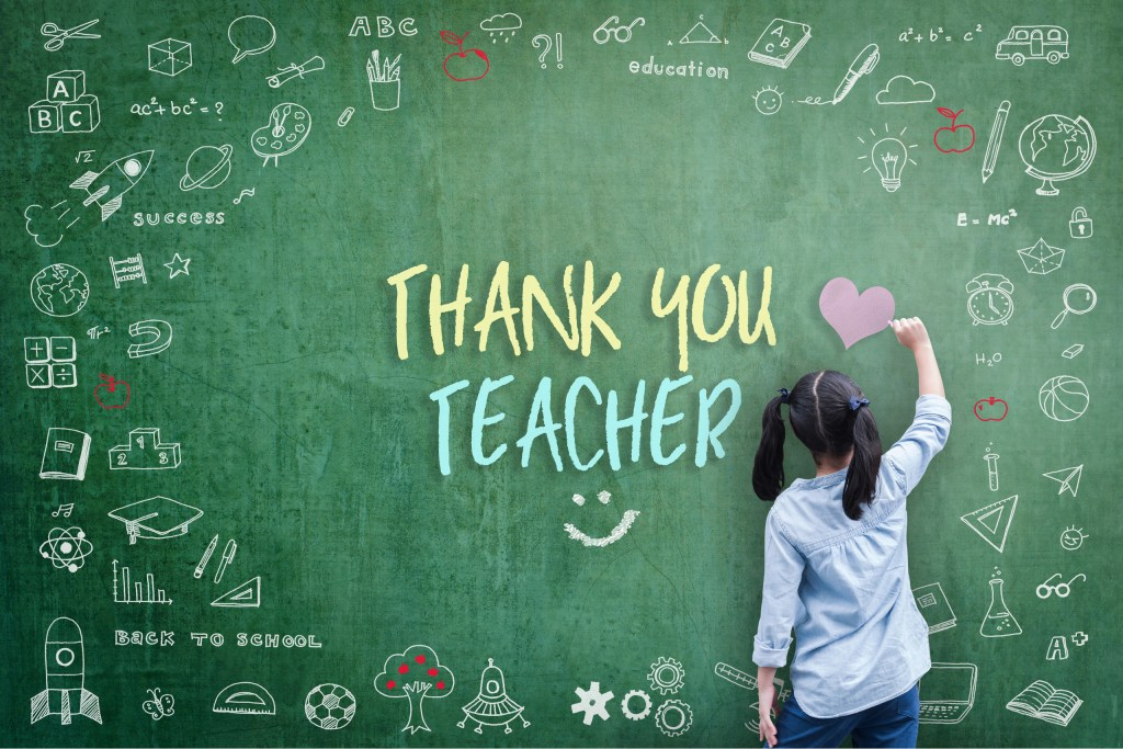 Thank you Teacher written on the chalk board by young female student