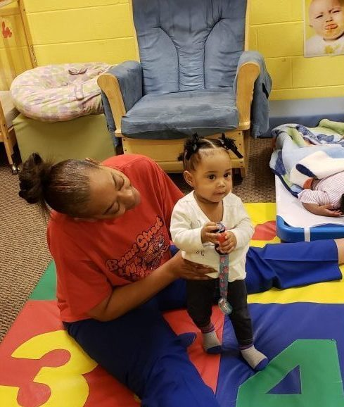 Head Start Instructor caring for young head start girl