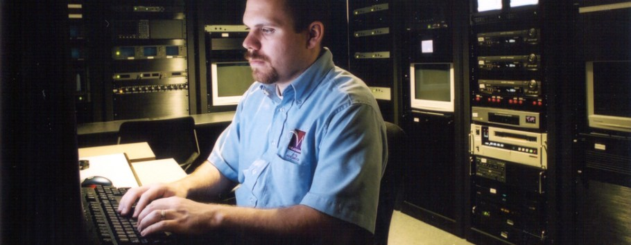 photo of man seated at keyboard in media control room