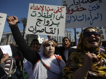 "2012- Moroccan women hold signs saying, ""Stop abusing girls"" to protest the lack of laws against child marriage."